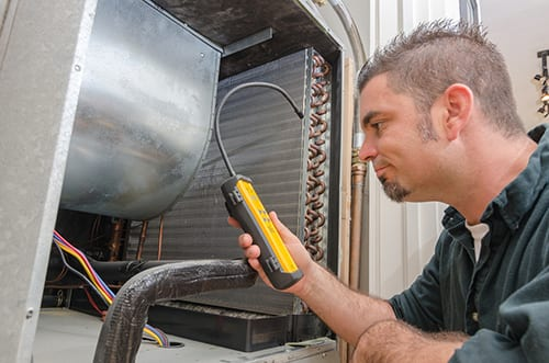 HVAC technician checking refirgerant levels