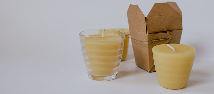 Beeswax candles sitting near container