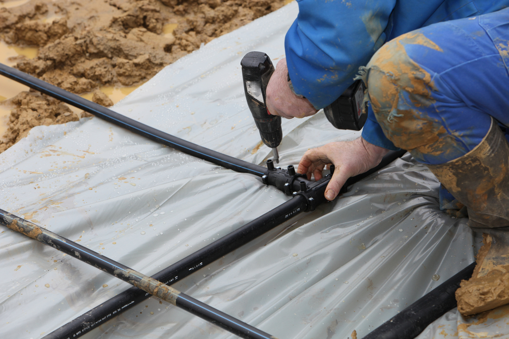 A contractor installs geothermal pipes in the ground