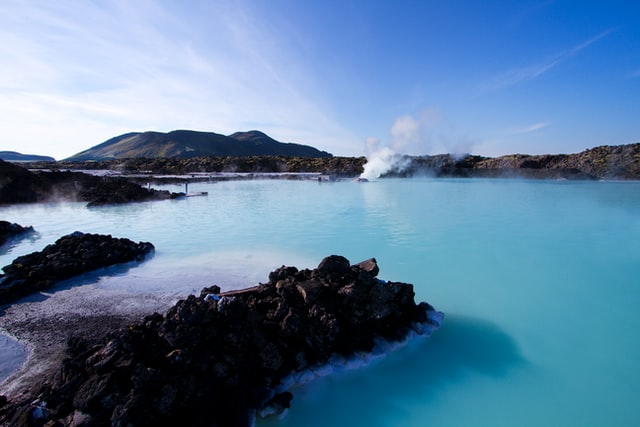 A hot spring in the Blue Lagoon Geothermal Spa in Iceland with steam coming off of the hot water into the cold air