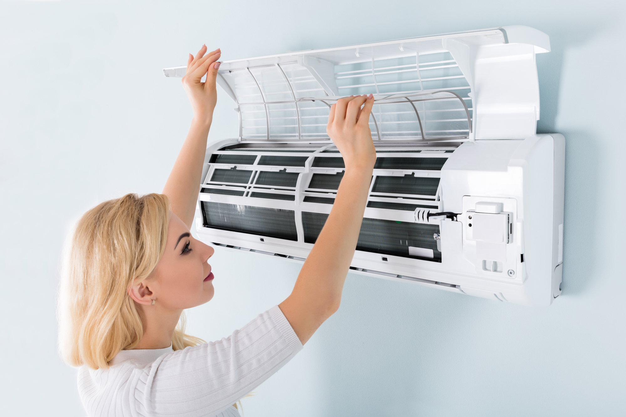 Woman cleaning ac filter