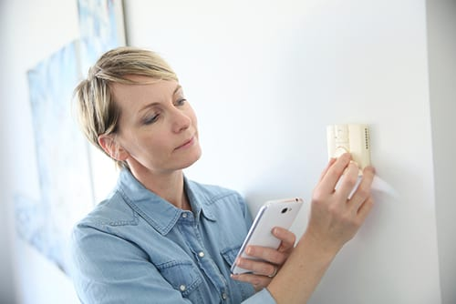 Woman inspecting thermostat