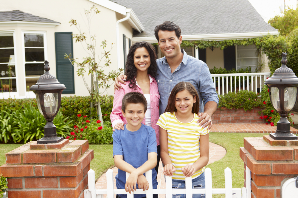 Happy family smiling outside their home