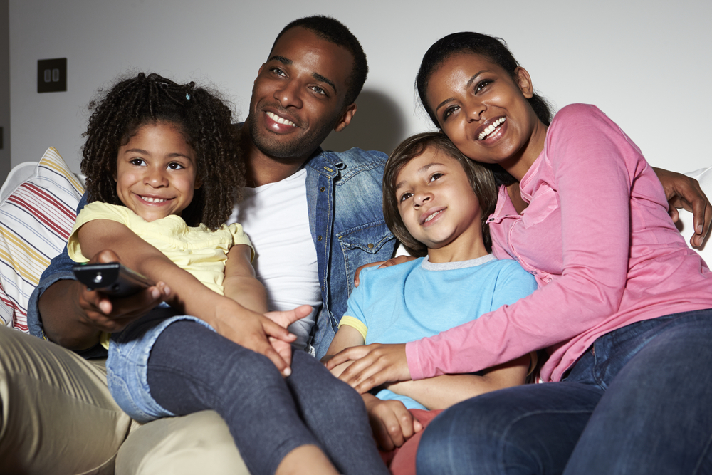 Family watching television together smiling