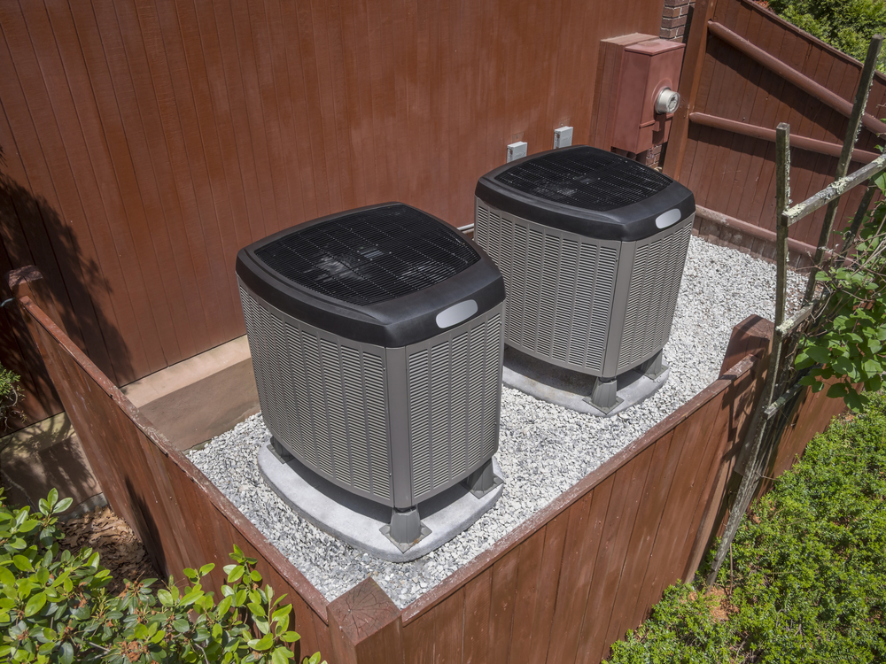HVAC units outside of a home with a fence enclosing them