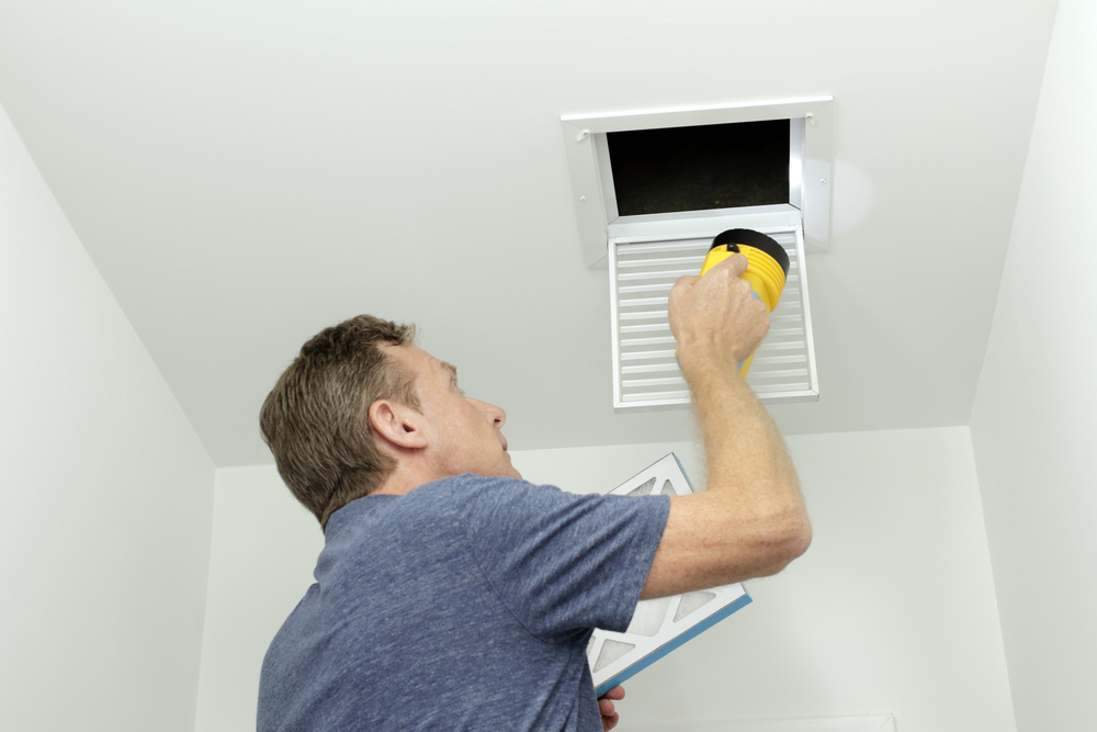 Man inspecting air ducts in a home