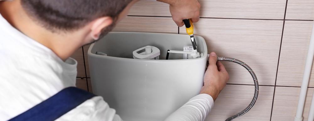 Plumber working on toilet float